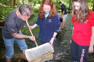 Professor Peter Bayers of the English Department helps students gather specimens from the Mill River in Fairfield, CT to determine its overall health.